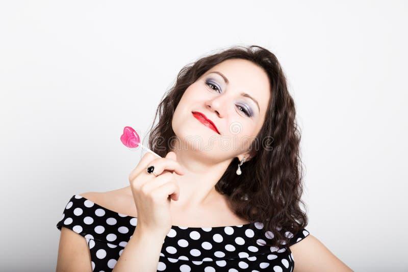 Retrato da jovem mulher bonita feliz que lambe doces doces e que expressa emoções diferentes Mulher bonita com coração imagem de stock royalty free