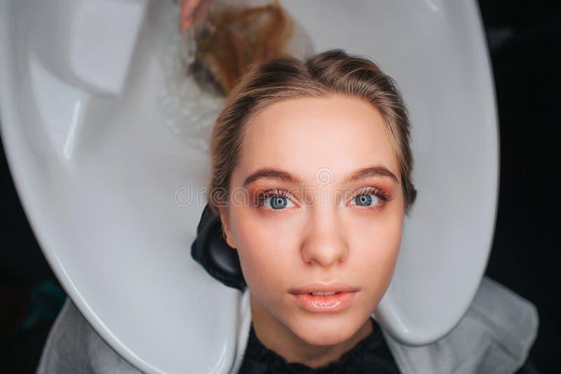 Retrato da jovem mulher bonita loura que senta-se no dissipador da lavagem do cabelo branco e que espera um cabeleireiro Cabelo d foto de stock