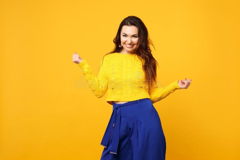 Retrato da jovem mulher bonita na camiseta, calças azul que olha a câmera, mãos de espalhamento isoladas na laranja amarela foto de stock