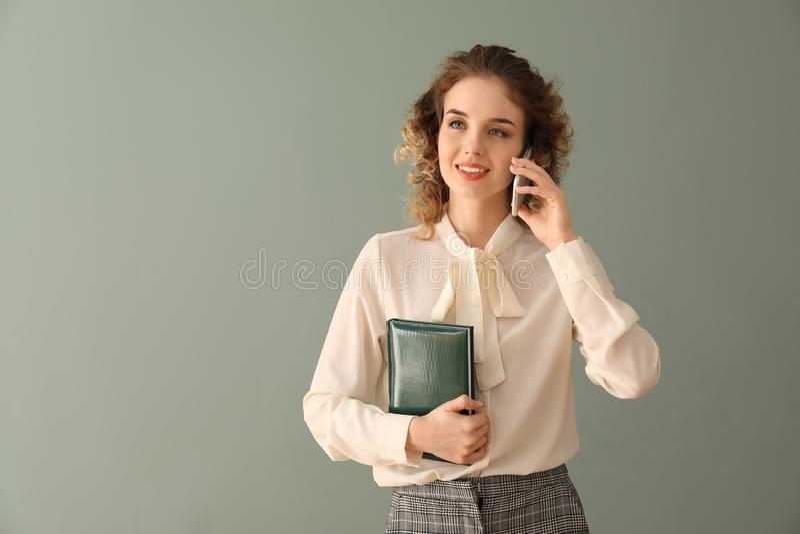 Retrato da jovem mulher bonita na roupa formal que fala pelo telefone no fundo da cor foto de stock