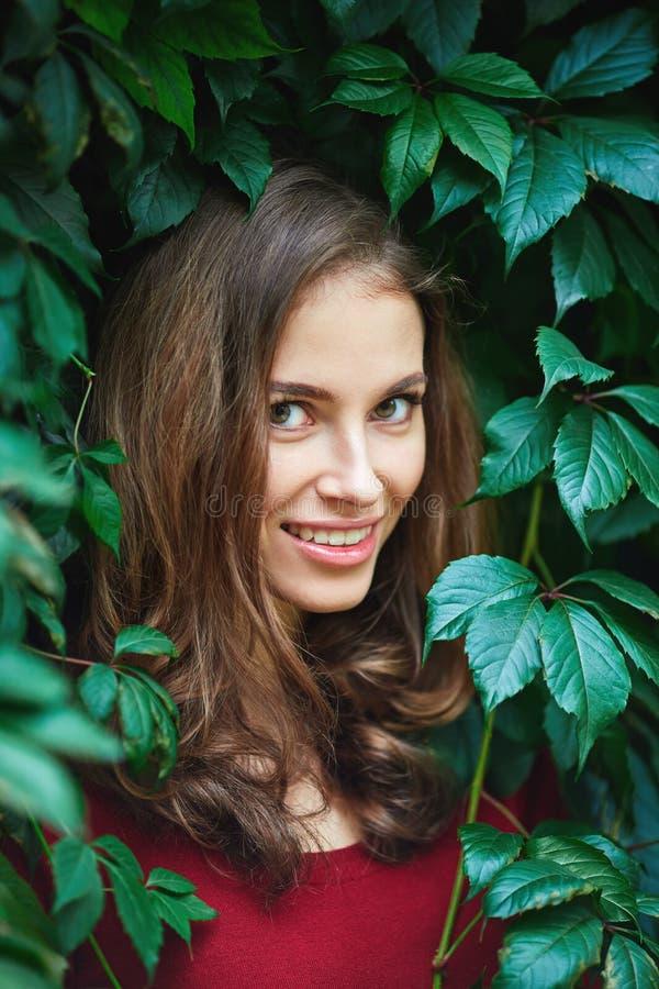 Retrato da jovem mulher bonita nas folhas selvagens foto de stock royalty free