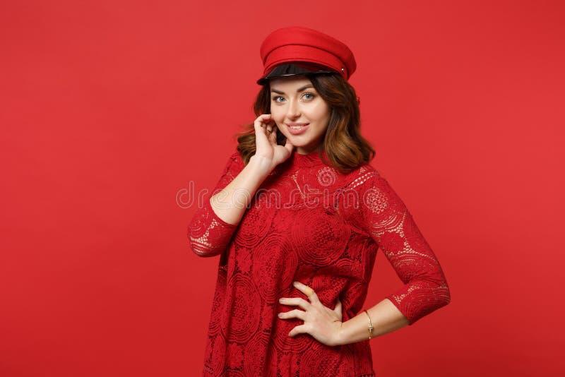 Retrato da jovem mulher bonita no vestido do laço, tampão que olha a mão da terra arrendada da câmera perto da cara na parede ver fotografia de stock royalty free