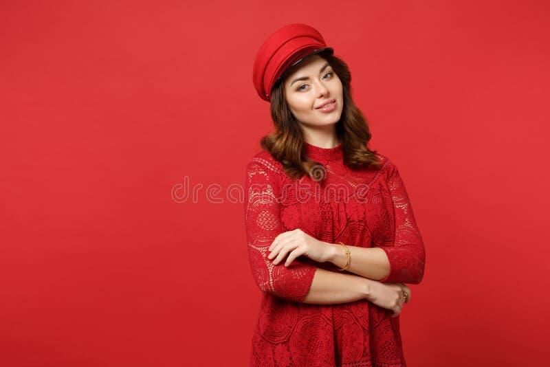 Retrato da jovem mulher bonita no vestido e no tampão do laço que olham a câmera que mantém as mãos dobradas no vermelho brilhant fotos de stock