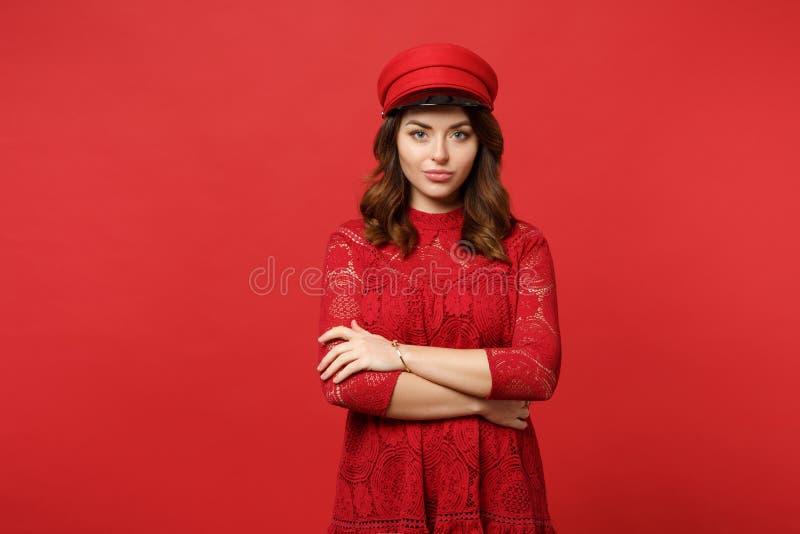 Retrato da jovem mulher bonita no vestido e no tampão do laço que olham a câmera, mantendo as mãos cruzadas no vermelho brilhante imagens de stock royalty free