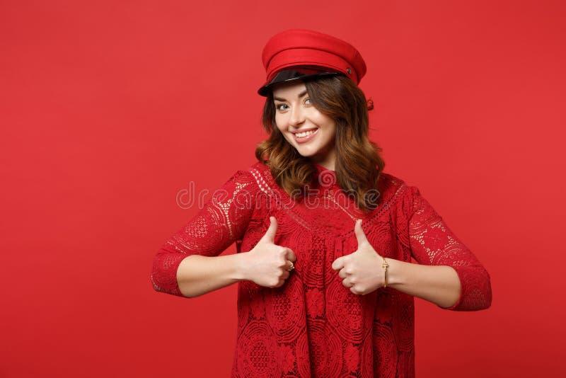 Retrato da jovem mulher bonita no vestido e no tampão do laço que olham a câmera, mostrando os polegares acima na parede vermelha fotografia de stock