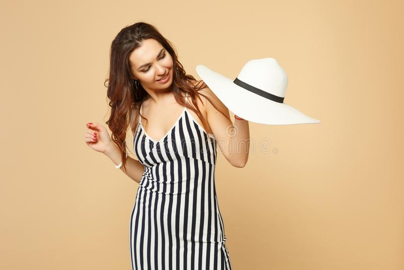 Retrato da jovem mulher bonita no vestido listrado preto e branco que guarda à disposição, olhando no chapéu no bege pastel imagens de stock royalty free