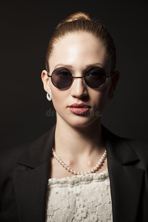 Retrato da jovem mulher bonita nos óculos de sol no backgro preto fotos de stock royalty free