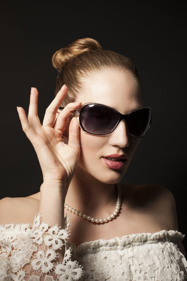 Retrato da jovem mulher bonita nos óculos de sol no backgro preto imagem de stock