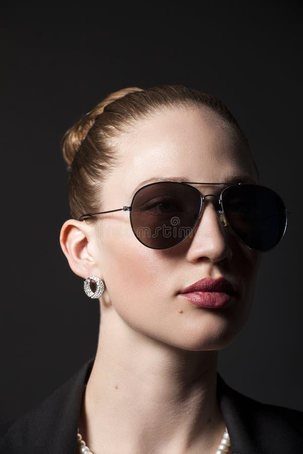 Retrato da jovem mulher bonita nos óculos de sol no backgro preto fotografia de stock