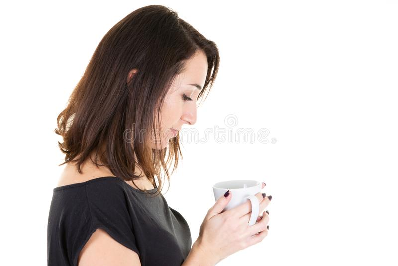 Retrato da jovem mulher bonita que bebe um copo do chá que olha a caneca imagem de stock royalty free