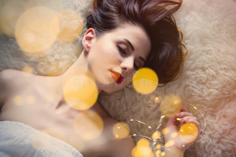 Retrato da jovem mulher bonita que encontra-se na cobertura macia com c fotos de stock royalty free