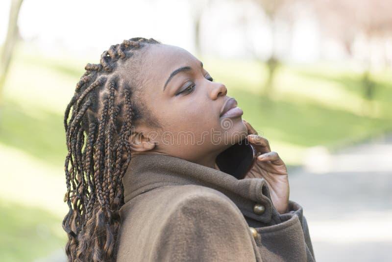 Retrato da jovem mulher bonita que fala pelo telefone, exterior imagem de stock