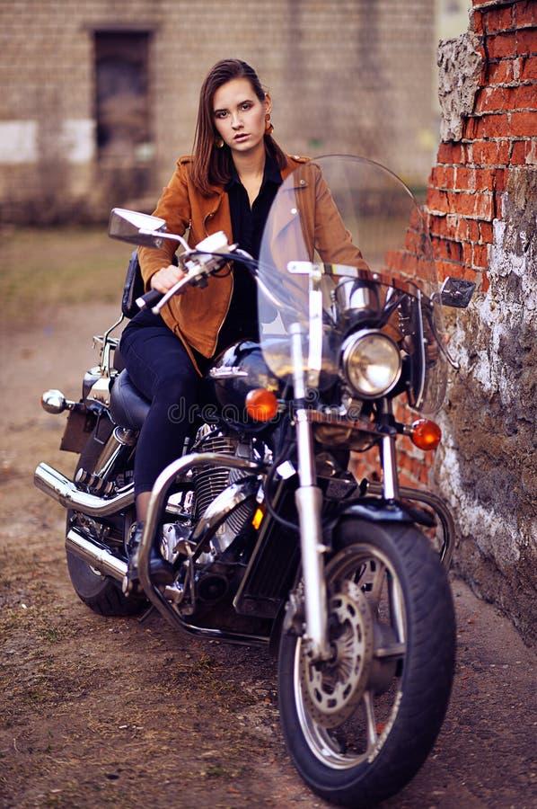 Retrato da jovem mulher bonita que levanta com motocicleta fotos de stock royalty free