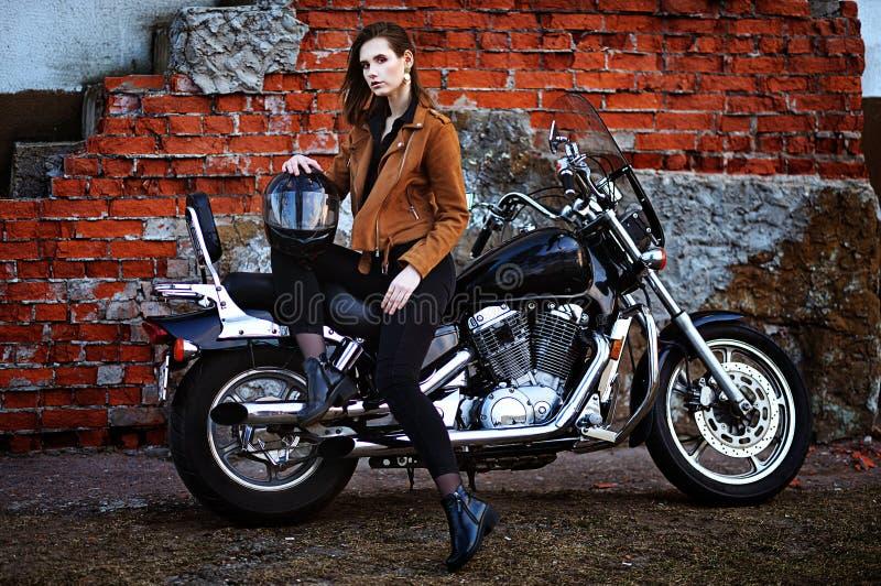 Retrato da jovem mulher bonita que levanta com motocicleta foto de stock royalty free