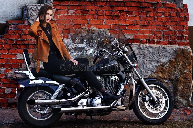 Retrato da jovem mulher bonita que levanta com motocicleta imagem de stock royalty free