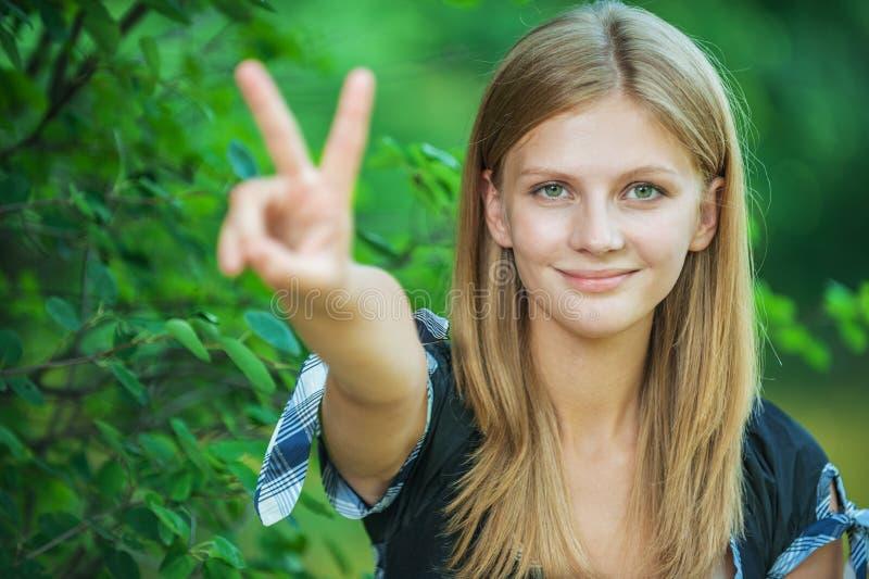Retrato da jovem mulher bonita que mostra o gesto do sinal da vitória fotografia de stock