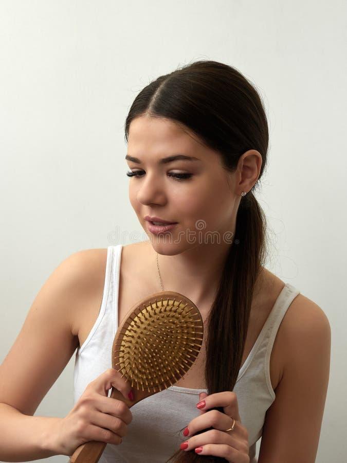 Retrato da jovem mulher bonita que penteia seu cabelo no fundo branco foto de stock