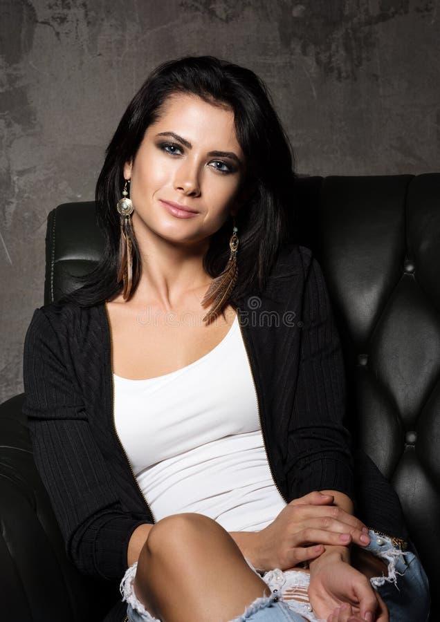 Retrato da jovem mulher bonita que senta-se em uma cadeira ou no sofá Brincos com penas fotos de stock royalty free