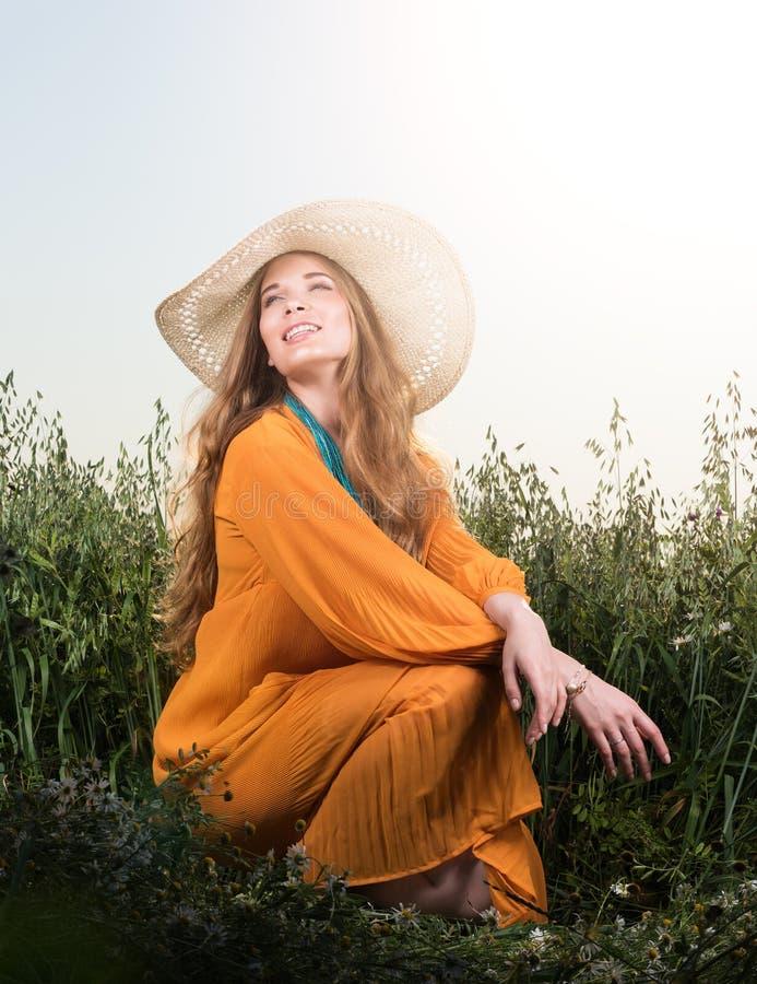 Retrato da jovem mulher bonita que senta-se na grama Chapéu e vestido vermelho imagens de stock royalty free