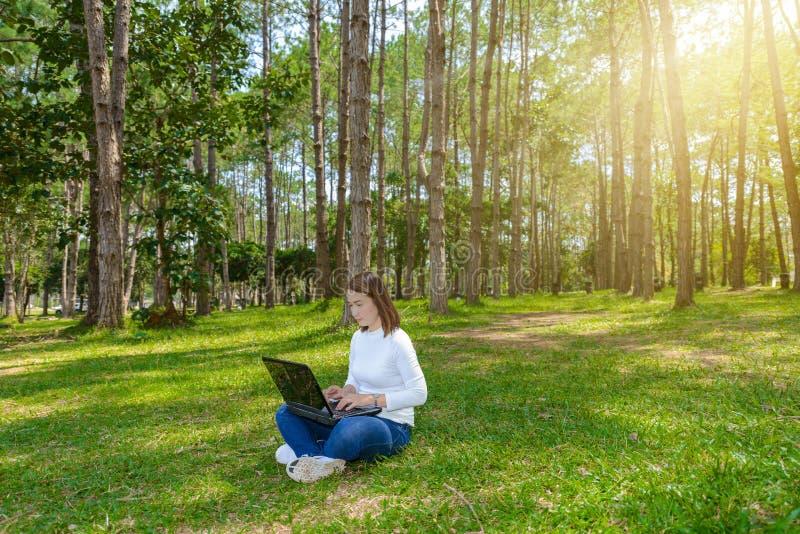 Retrato da jovem mulher bonita que senta-se na grama verde no parque com os pés cruzados durante o dia de verão ao usar o portáti foto de stock royalty free