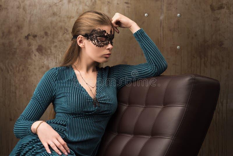 Retrato da jovem mulher bonita que senta-se no sofá Máscara preta fotografia de stock royalty free