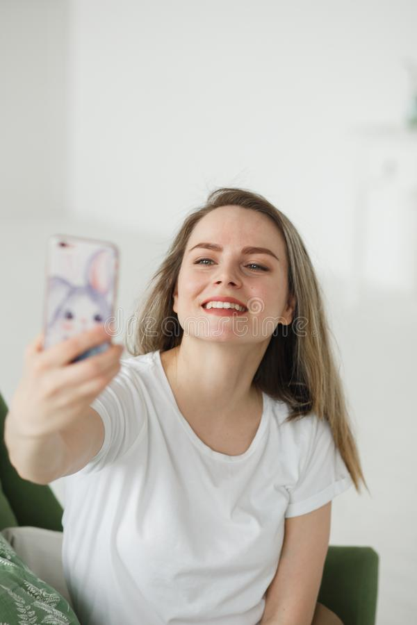 Retrato da jovem mulher bonita que toma o selfie na poltrona na sala de visitas clara fotografia de stock