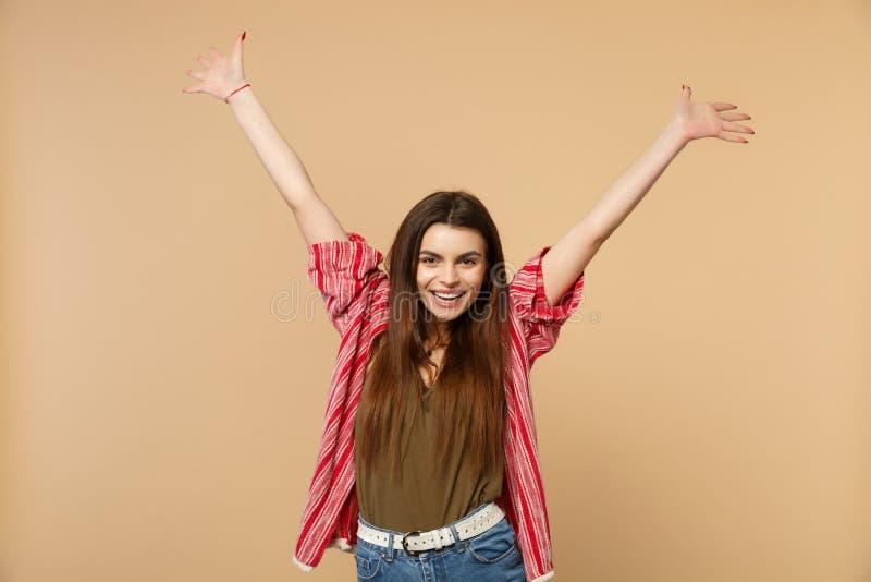 Retrato da jovem mulher bonito alegre na roupa ocasional que olha a câmera, mãos de aumentação isoladas na parede bege pastel fotos de stock royalty free