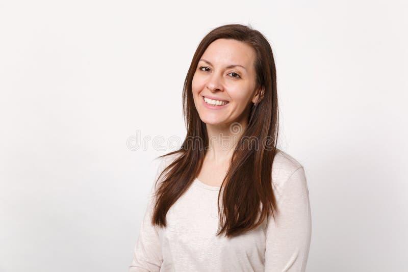 Retrato da jovem mulher bonito bonita de sorriso na roupa leve que está e que olha a câmera isolada na parede branca imagem de stock
