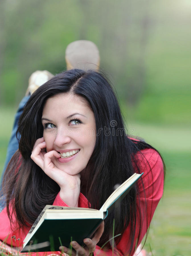 Retrato da jovem mulher bonito que lê um livro na grama no summ imagens de stock