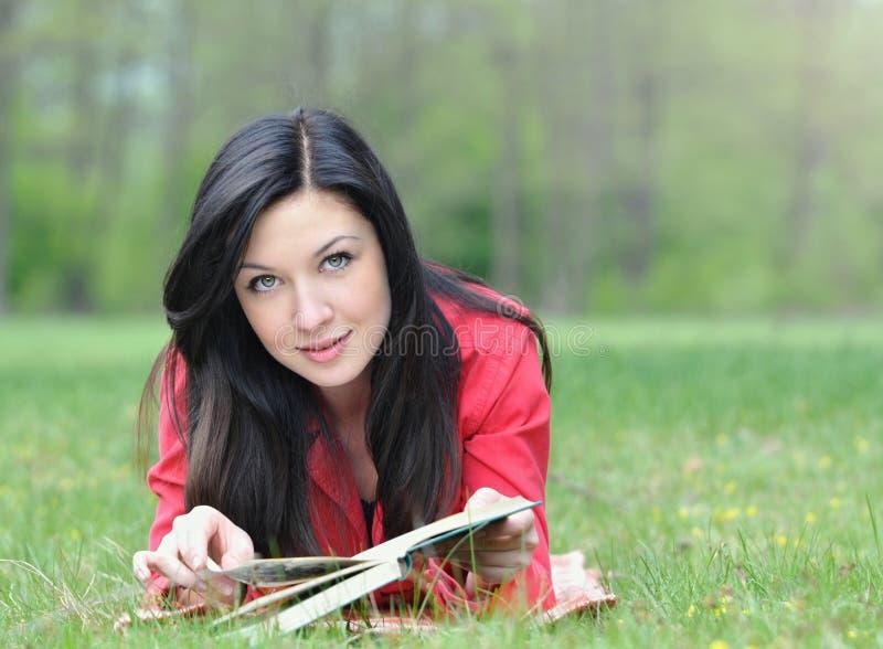 Retrato da jovem mulher bonito que tem um resto com o livro na grama dentro fotografia de stock