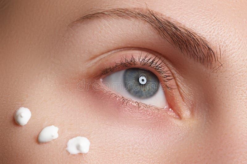Retrato da jovem mulher com a cara limpa fresca com pontos do creme hidratando sob o olho foto de stock