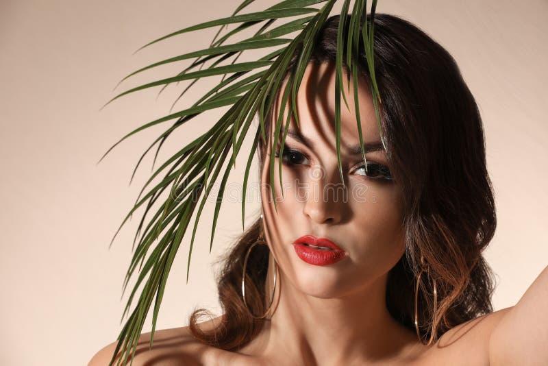 Retrato da jovem mulher com composição profissional bonita e da folha de palmeira no fundo claro fotografia de stock