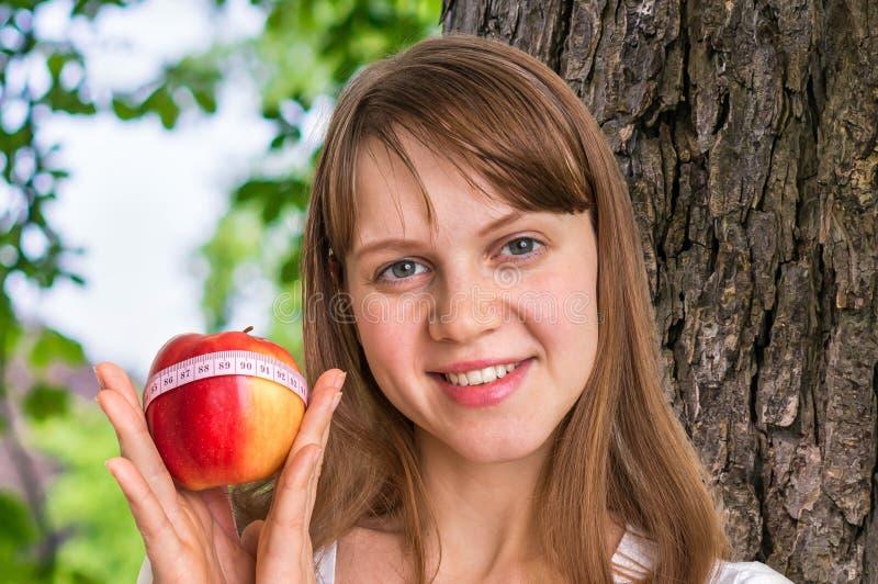 Retrato da jovem mulher com maçã fresca e medida da fita foto de stock royalty free