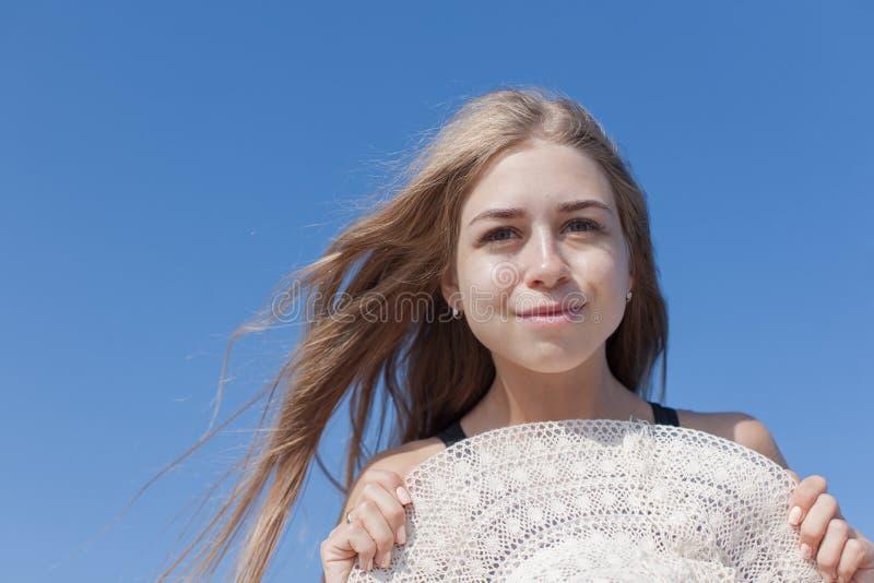 Retrato da jovem mulher com o chapéu do sol contra o céu foto de stock