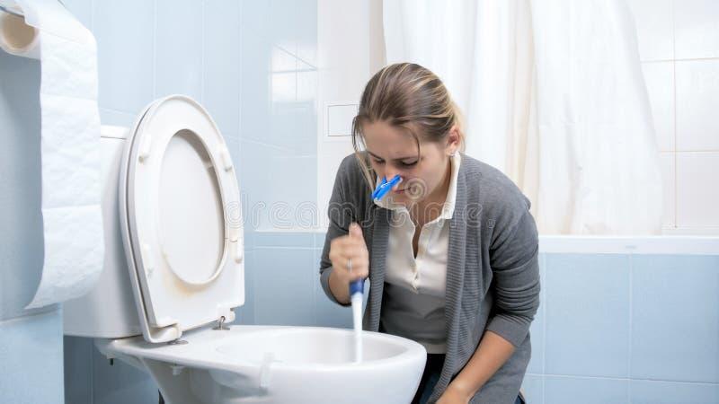 Retrato da jovem mulher com o pregador de roupa que fecha seu toalete de lavagem do nariz fotografia de stock royalty free