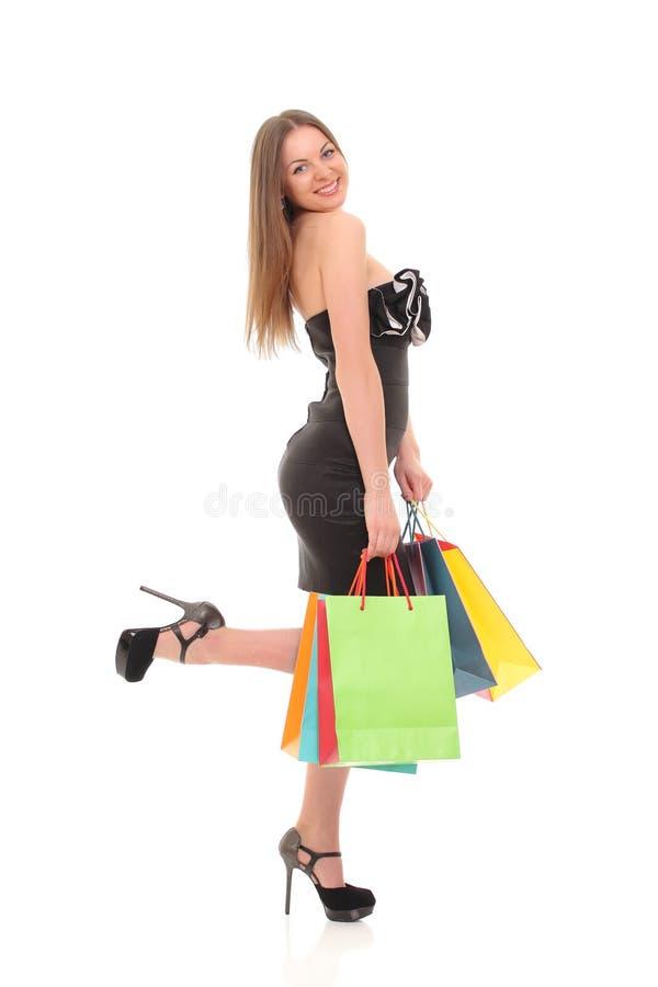 Retrato da jovem mulher com os sacos de compras contra o fundo branco imagem de stock royalty free