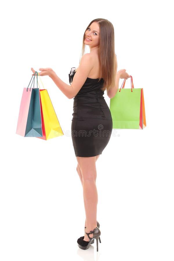 Retrato da jovem mulher com os sacos de compras contra o fundo branco fotografia de stock royalty free