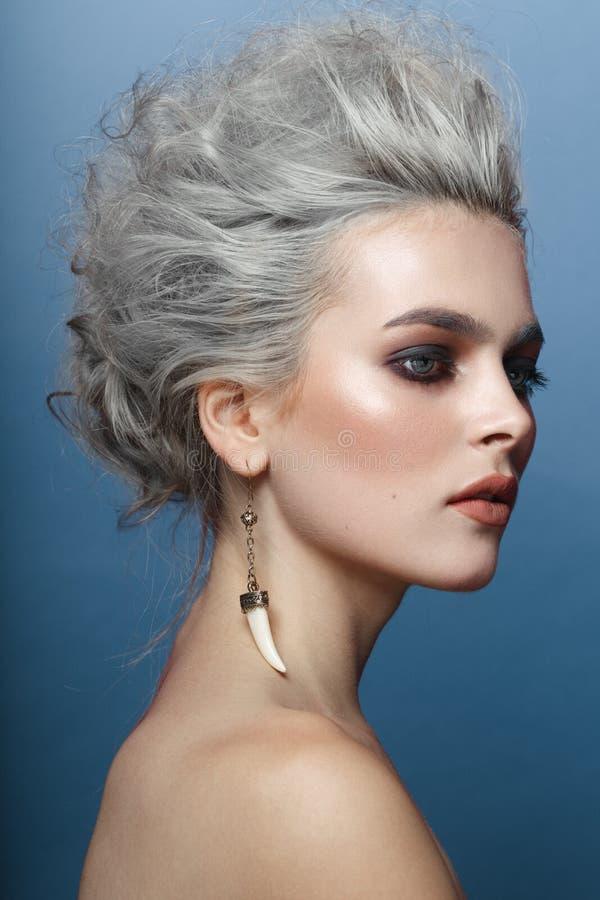 Retrato da jovem mulher com penteado, os olhos do smokey e composi??o cinzentos com os ombros despidos, isolados no fundo azul fotografia de stock