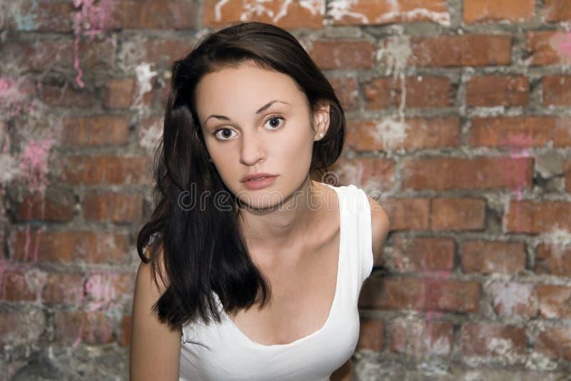 Retrato da jovem mulher com uma parede de tijolo no backgro imagens de stock royalty free