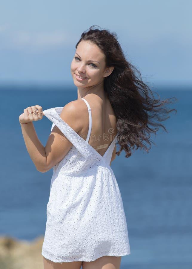 Retrato da jovem mulher contra o mar no dia nebuloso imagem de stock
