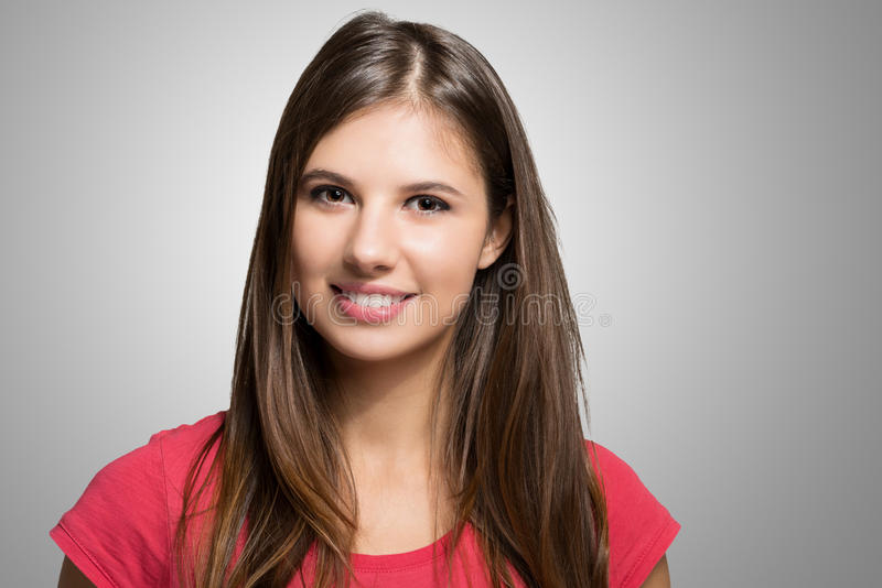 Retrato da jovem mulher contra um fundo cinzento fotos de stock