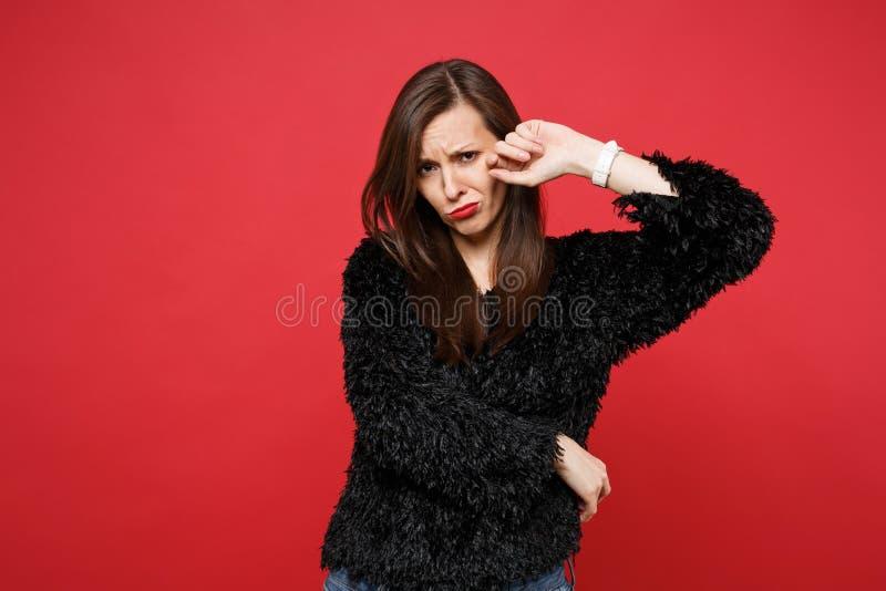 Retrato da jovem mulher de grito virada na posição preta da camiseta da pele e dos rasgos da limpeza isolados na parede vermelha  imagem de stock royalty free
