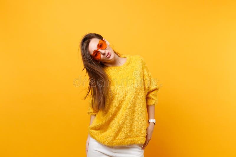 Retrato da jovem mulher de sorriso alegre na camiseta da pele, nas calças brancas e nos monóculos alaranjados do coração isolados fotografia de stock