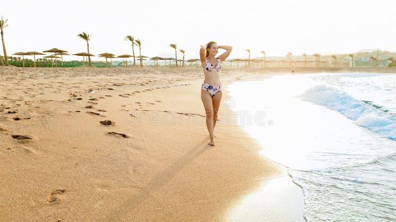 Retrato da jovem mulher de sorriso bonita com cabelo longo que anda na praia arenosa do mar contra o céu e a vista do por do sol fotos de stock