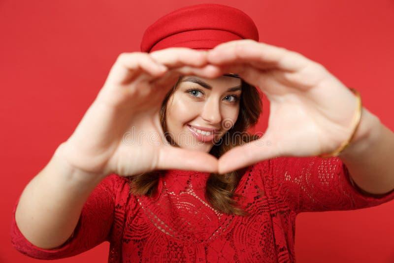 Retrato da jovem mulher de sorriso bonita no tampão do vestido do laço que mostra o coração da forma com mãos na parede vermelha  foto de stock