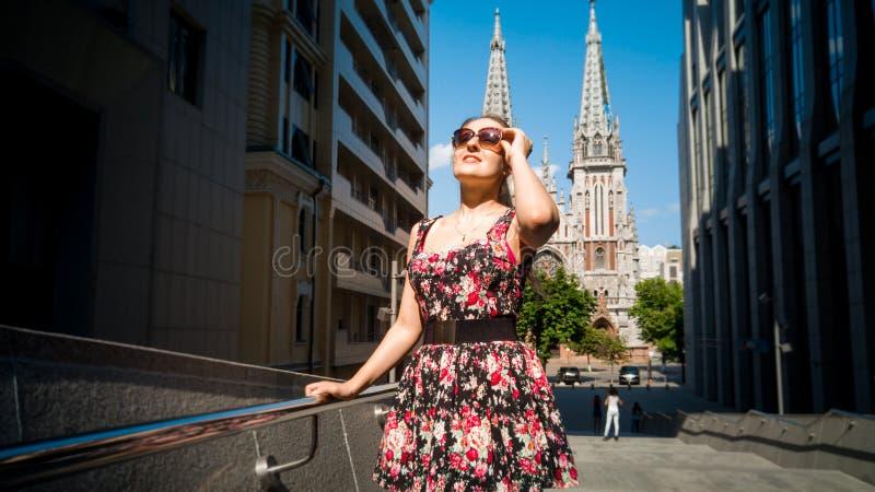 Retrato da jovem mulher de sorriso bonita nos ?culos de sol que levantam contra a constru??o moderna e a catedral cat?lica velha  foto de stock royalty free