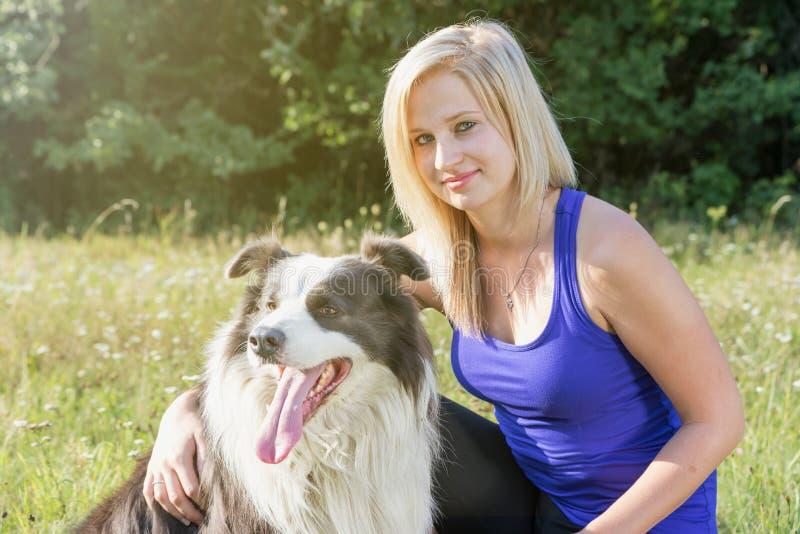 Retrato da jovem mulher de sorriso com seu border collie fora foto de stock royalty free