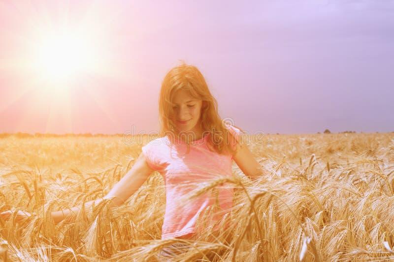 Retrato da jovem mulher de sorriso feliz que anda através do campo e fotos de stock royalty free
