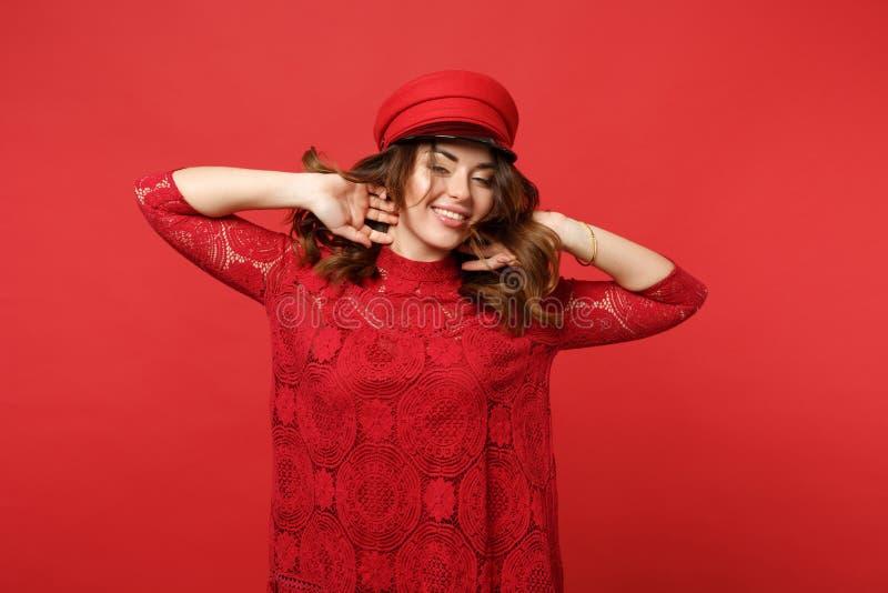 Retrato da jovem mulher de sorriso impressionante no vestido e no tampão do laço que guardam as mãos no cabelo isolado na parede  foto de stock royalty free