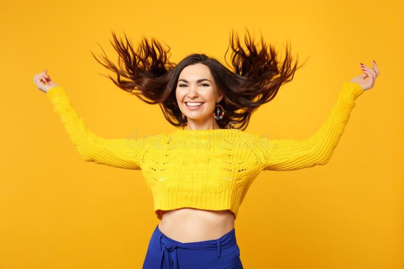 Retrato da jovem mulher de sorriso na camiseta, calças azul com as mãos de espalhamento de fluxo do cabelo isoladas na laranja am imagem de stock